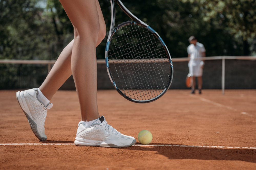 A couple being active by playing tennis. The woman is about to serve.