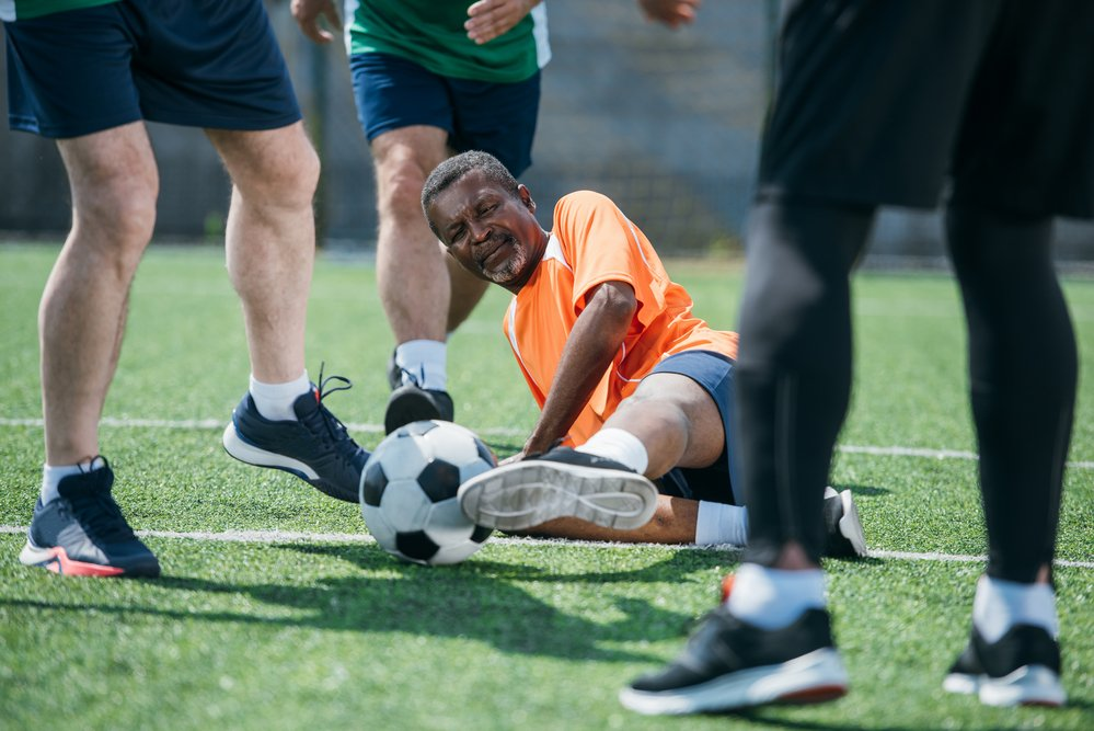 An older man on the ground, kicking a soccer ball, surrounded by other soccer players
