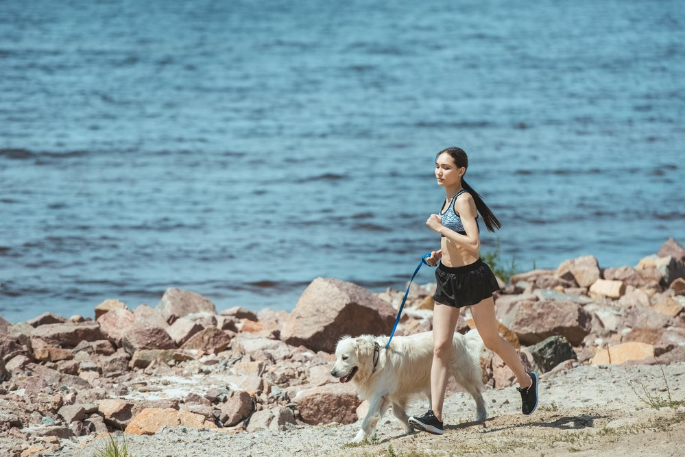 A young woman running outside, along a stone=walled seafront, with her dog. She is being environmentally fit.