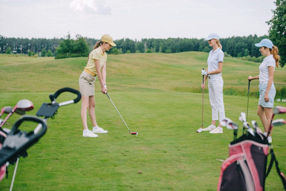 2 women playing golf. One teeing off and with correct posture so that she doesn't get any golf injuries