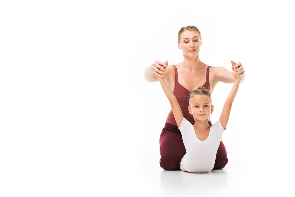 A young woman helping a little girl with her gymnastics pose