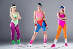 3 women in flouro exercise clothing, ready to do aerobics