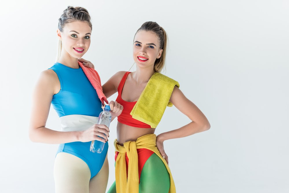 2 women in brightly coloured exercise clothes, waiting for an aerobics class to start
