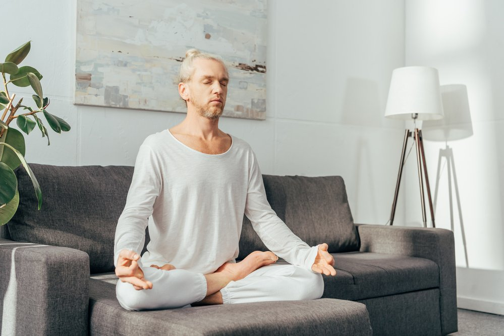 A man practising Hatha yoga at home, sitting on the sofa in the lotus position.