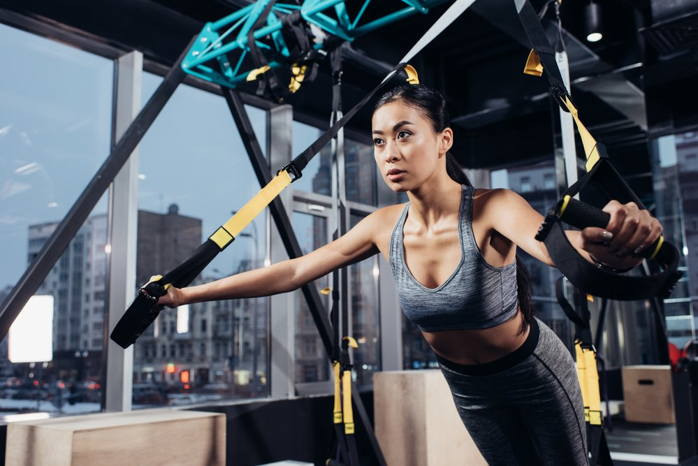 A young woman practising resistance training in a gym