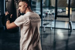 A man in a white t-shirt in a gym. He is a personal trainer. He runs bootcamps and outdoor fitness programs.