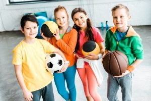 A group of children holding a variety of balls from different sports. They sre ready to play safer sport with new children guidelines
