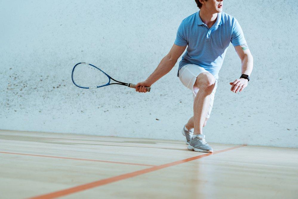 A man playing squash on a squash court