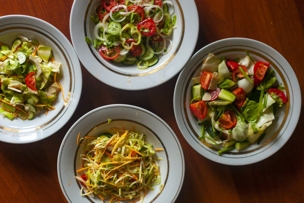 Several salads with vegetables and greens. Healthy food concept. Mixed vegetables salad. Eating clean can help with conditions like acne