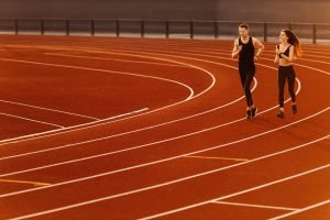 2 people running on a track, showing what is needed to prevent injuries with preseason training