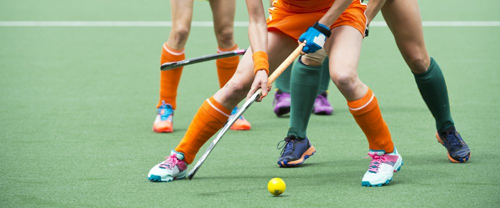 field hockey players challenge one another in a midfield battle on a hockey pitch