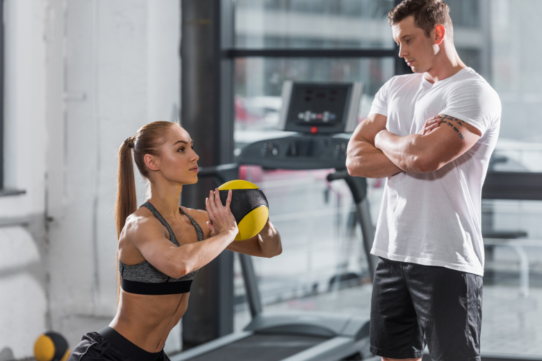 Personal trainer supervising female client doing squats with an exercise ball