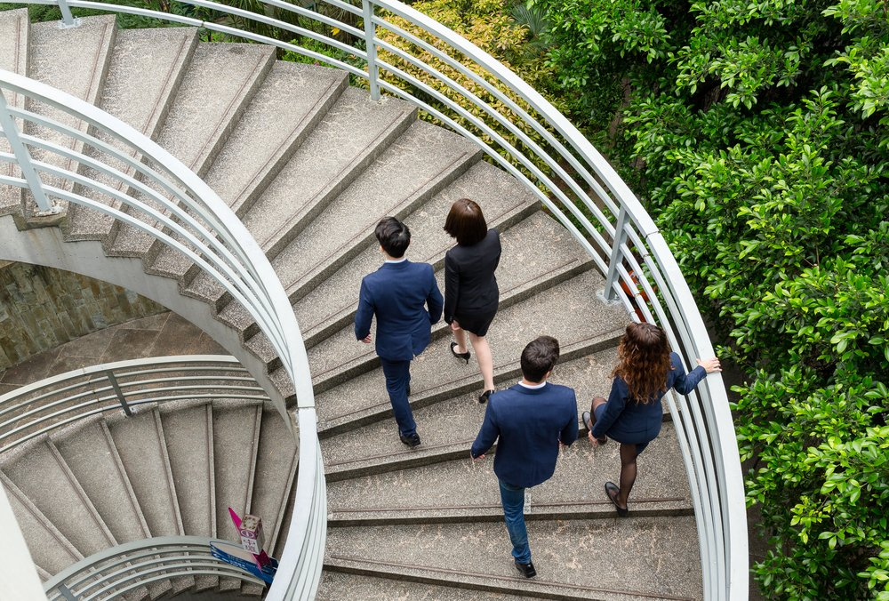 Business people burning calories by using the stairs rather than the lift.
