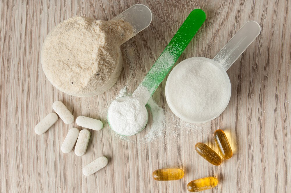 Bodybuilding supplements - scoop of protein, bcaa and creatine, omega3 in pills on wooden background