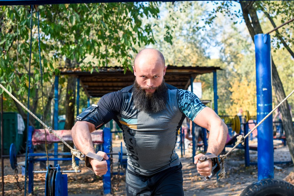 A muscular, bearded man doing resistance training as part of his strength training regime.