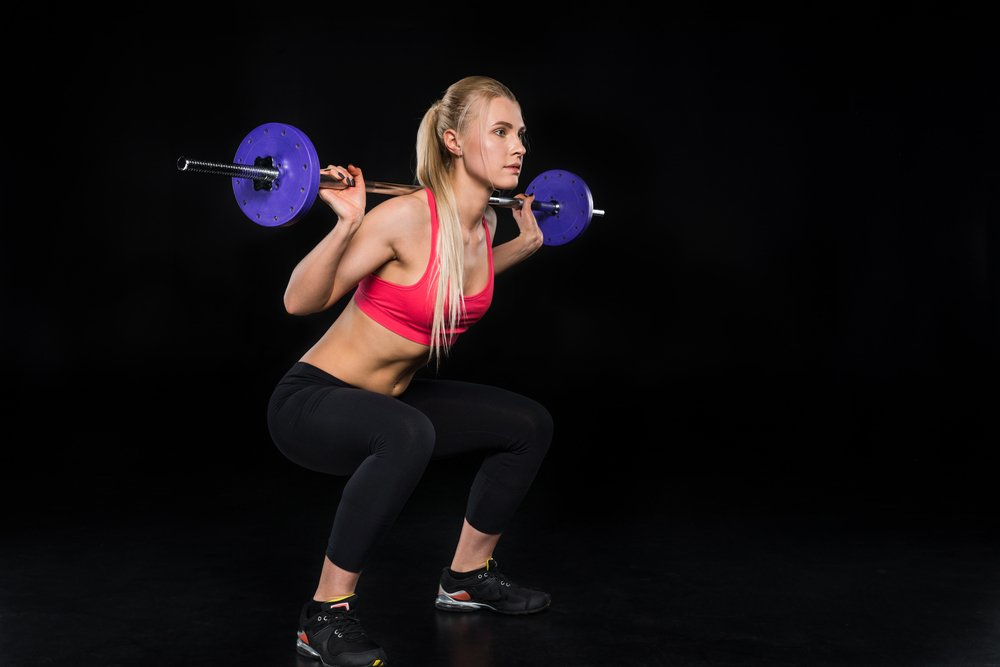 A fit young woman exercising with a barbell, using the crossFit training method.