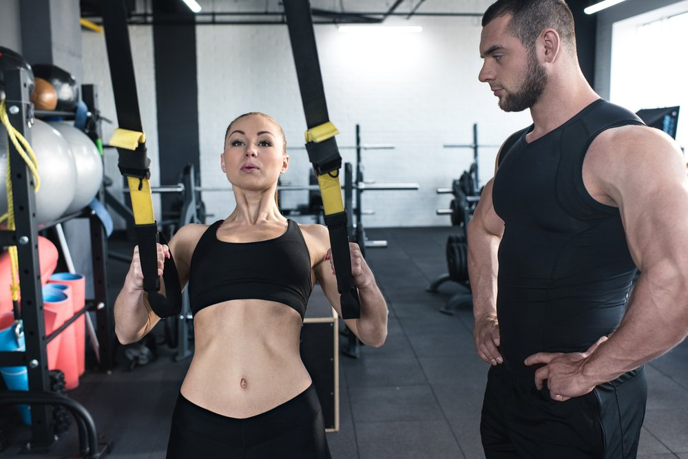 A sports woman training in a gym with a fitness coach.