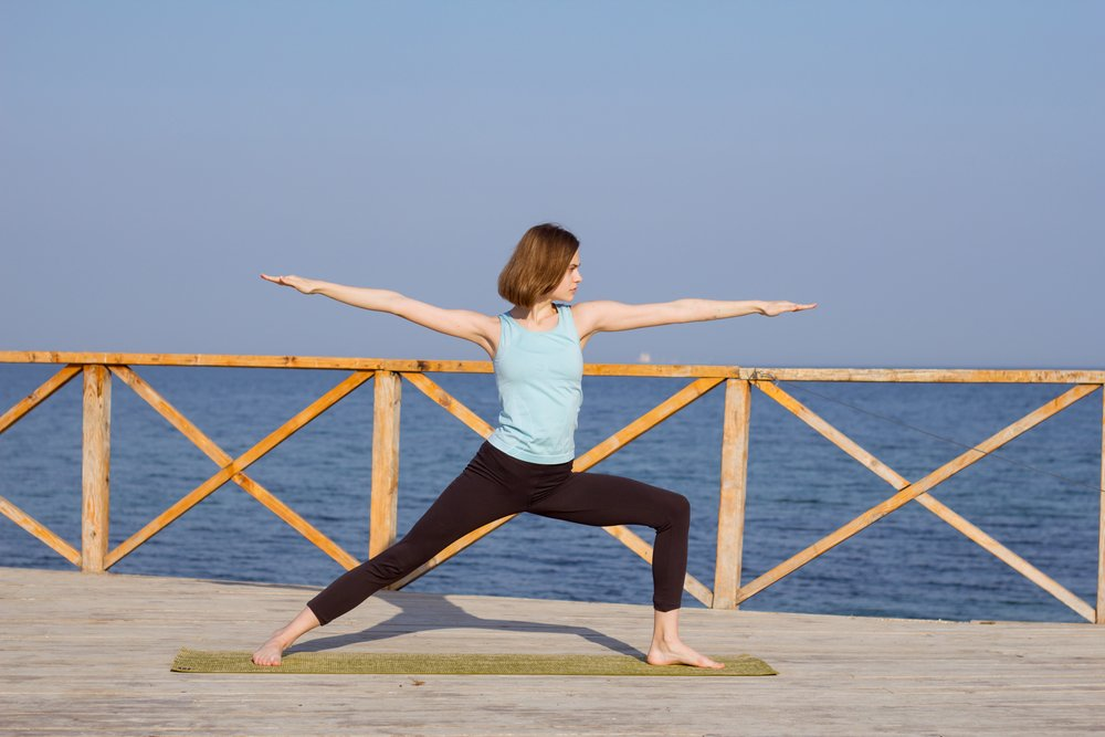 A young woman doing the warrior yoga pose and demonstrating her core strength.