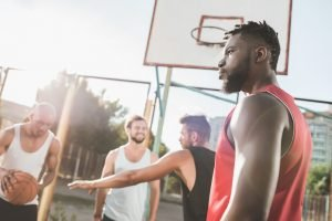 A group of men playing basketball on a court. They are about to get fit for basketball.