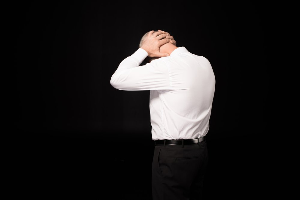 The rear view of a man in a white shirt, clasping the nape of his neck. He has chronic back and neck pain.