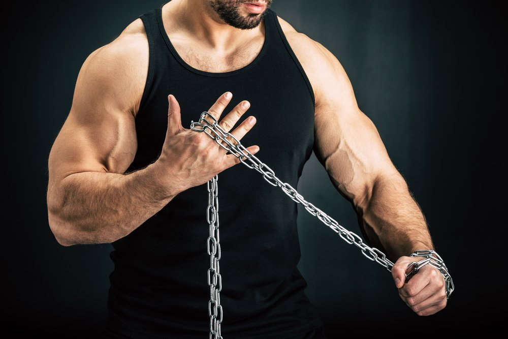 A fit, muscular man in close up, holding a metal chain. Bodybuilding supplements can help with muscle development.