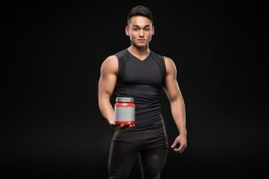 A muscular young man wearing black, on a black background, holding a jar of protein powder.