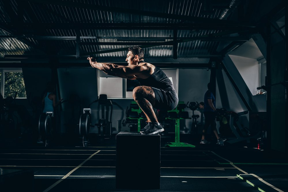 A sportsman doing a squat on a cube in a gym.