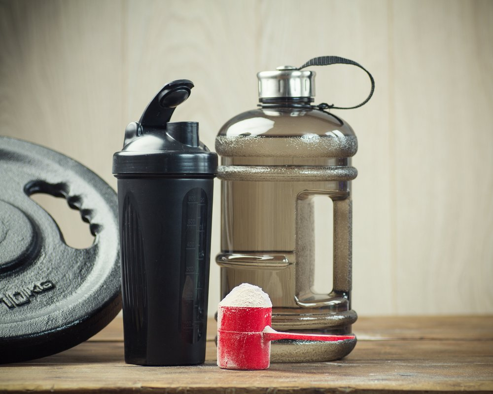 A weight, a bottle of water, a scoop of protein powder and a protein shaker.