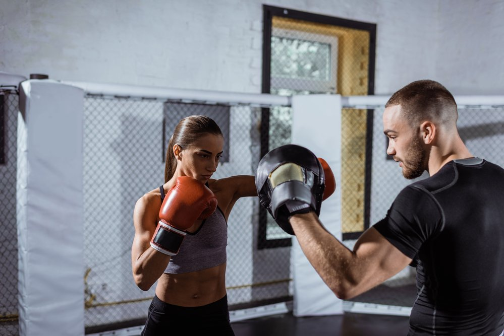 A woman boxing in a gym with her fitness coach