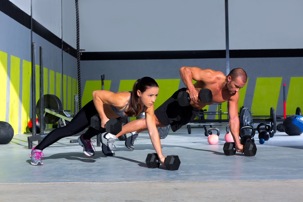 A fit woman and man doing push ups with weights as part of a strength training program