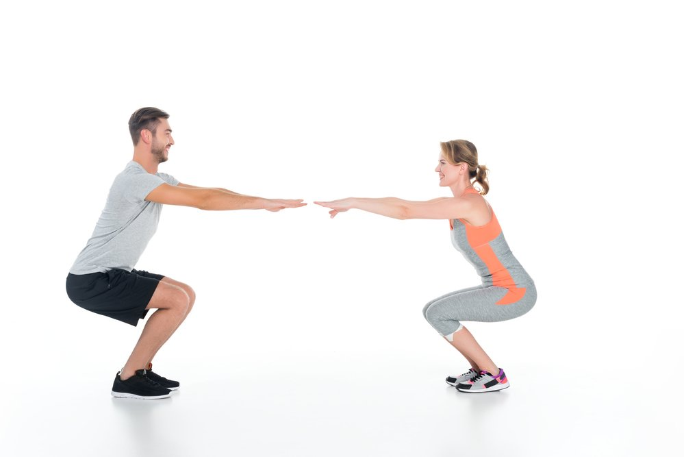 A couple doing squats facing one another. Just do something!