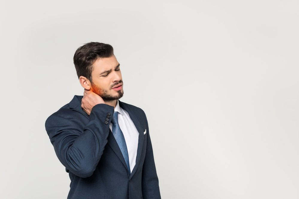 A young businessman in a suit, clutching his neck. He has chronic back and neck pain.