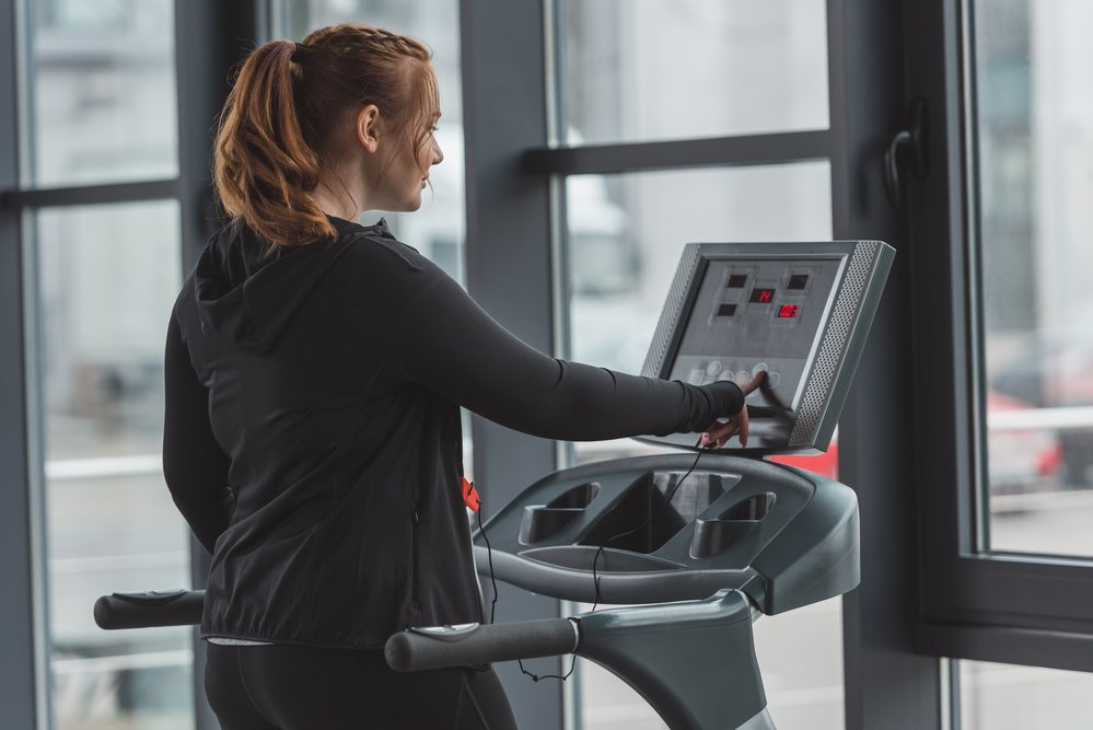 A young woman adjusting the controls on a running machine. You can measure calories for weight loss on some machines
