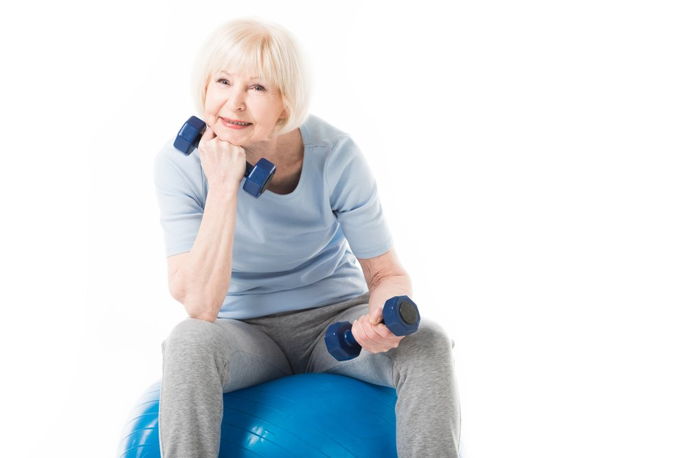 An older woman, sitting on a balance ball, holding dumbbells. How do you avoid injury going into a new exercise routine?