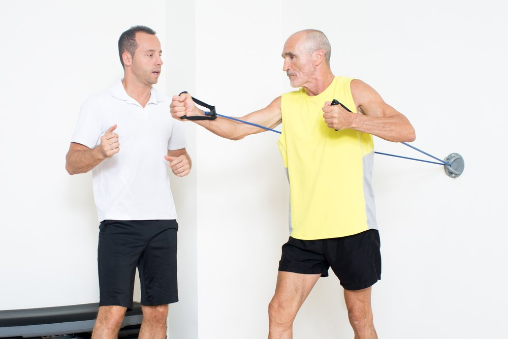 A personal trainer helps an older man with his exercise regime. A personal training career change.