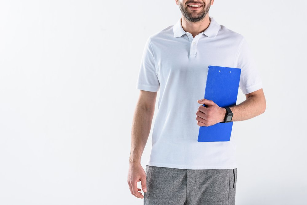 Cropped photo of a smiling physiotherapist holding a  clipboard. Getting exercise and therapeutic professionals in sync isn't easy.