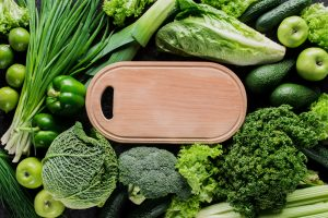 A wooden platter surrounded by lots of beautiful green veg. Perfect for a veggie breakfast bowl for one