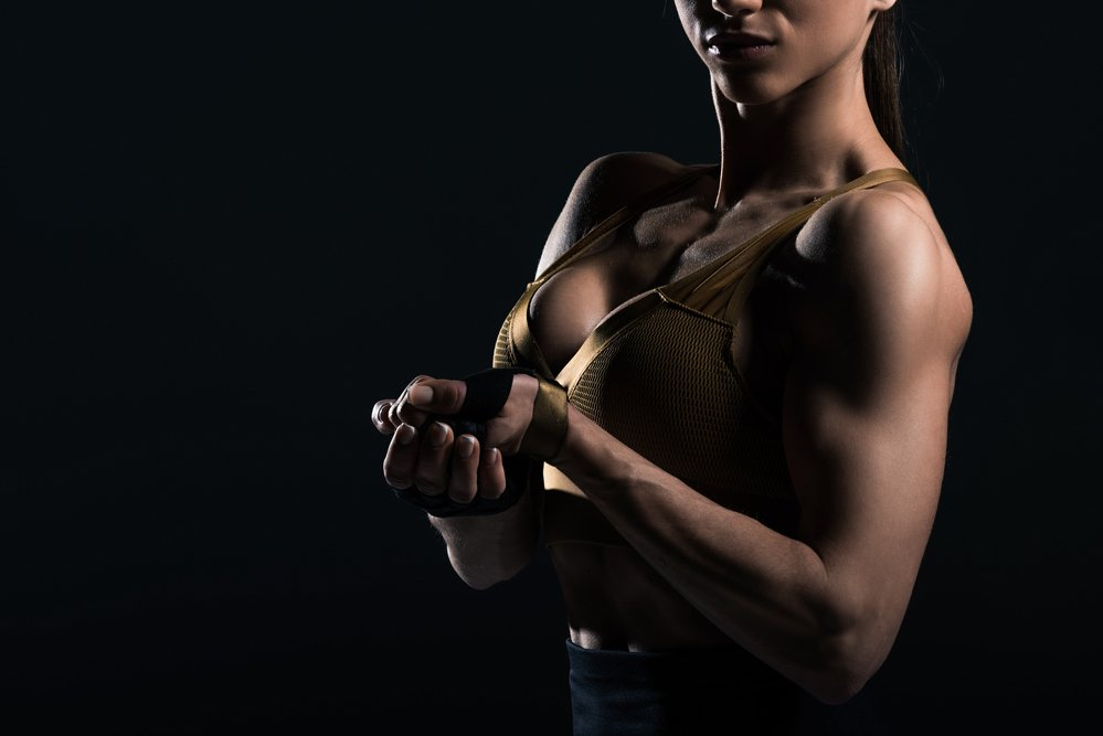 Close of a fit, muscular woman made strong by protein powder.