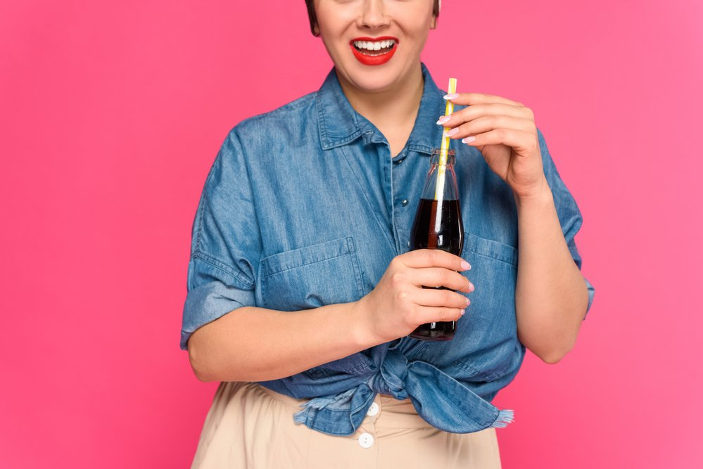 A smiling woman holding a glass bottle containing coke. Trying to lose stomach flab won't work if you keep drinking coke etc