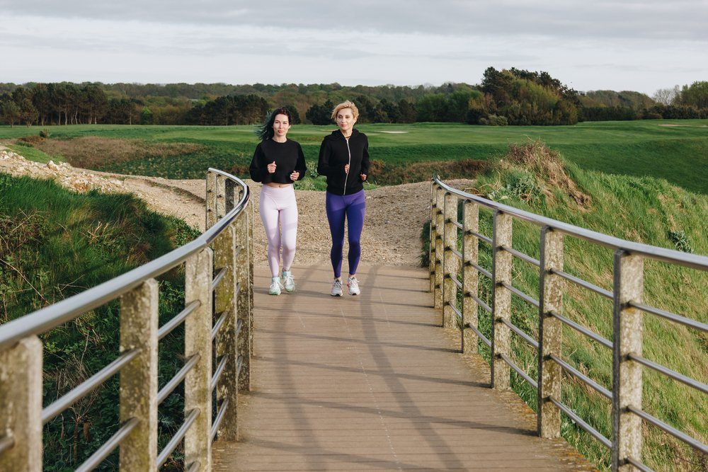 2 women, jogging towards a bridge on a country setting. Just do something to get moving.