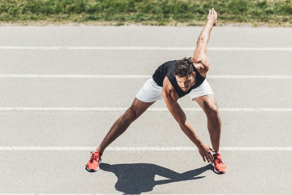 A young sportsman stretching on a running track. He needs to take care to avoid exertional rhabdomyolysis
