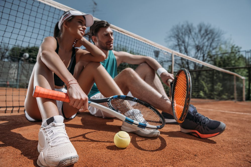 A young couple on tennis clothes, with tennis racquets sitting on a clay court next to a tennis net.