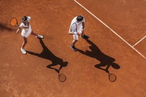 High angle view of a young sporty couple playing mixed couple tennis on a clay court
