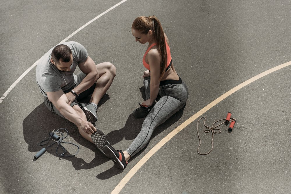 Overhead shot of 2 young, fits sports people, doing post-run stretches on a sports track.