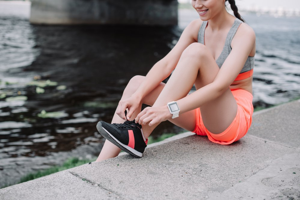 Cropped view of a sports woman tying the laces on her running shoes, next to a canal.