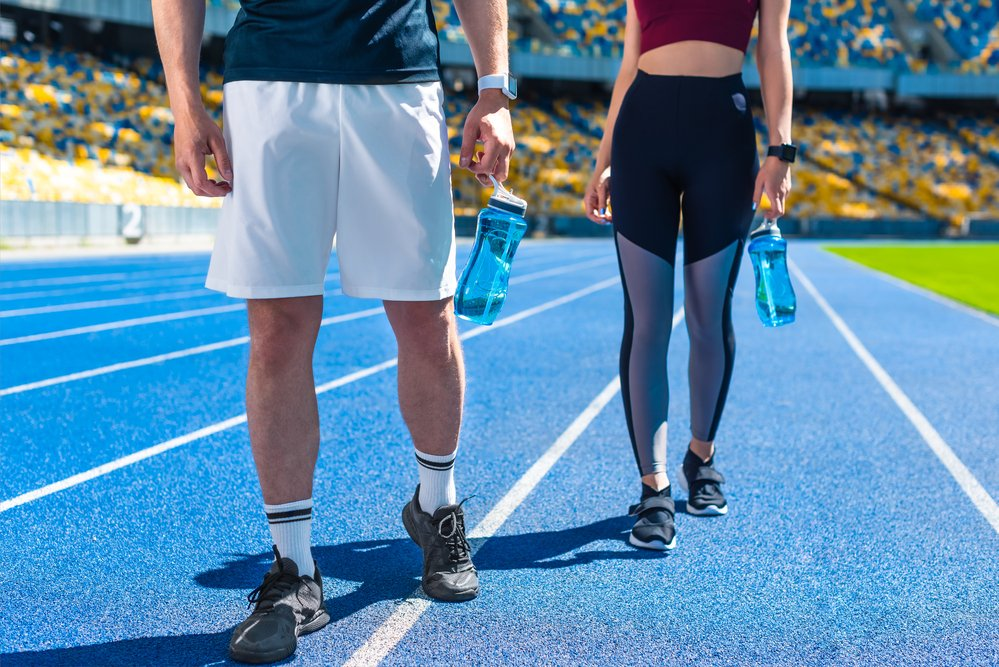 A cropped image of a personal trainer and her client on a training track.