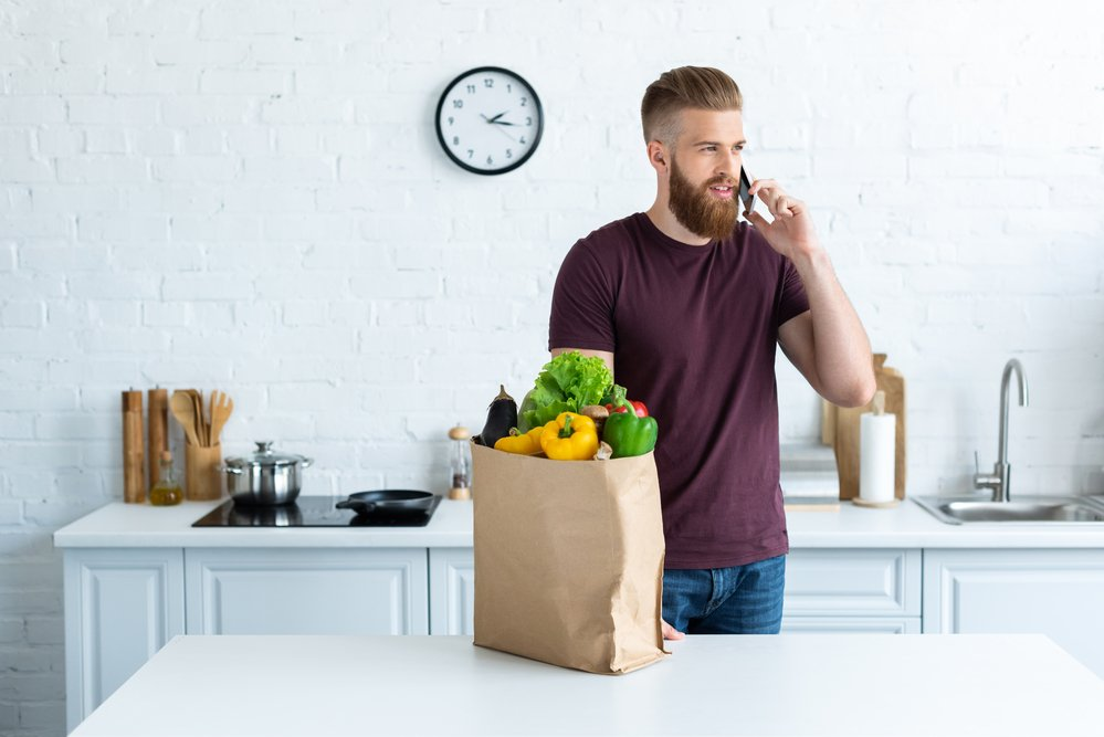 A bearded young man, with a bag of healthy grocerise in a kitchen. It's time for a census for our health