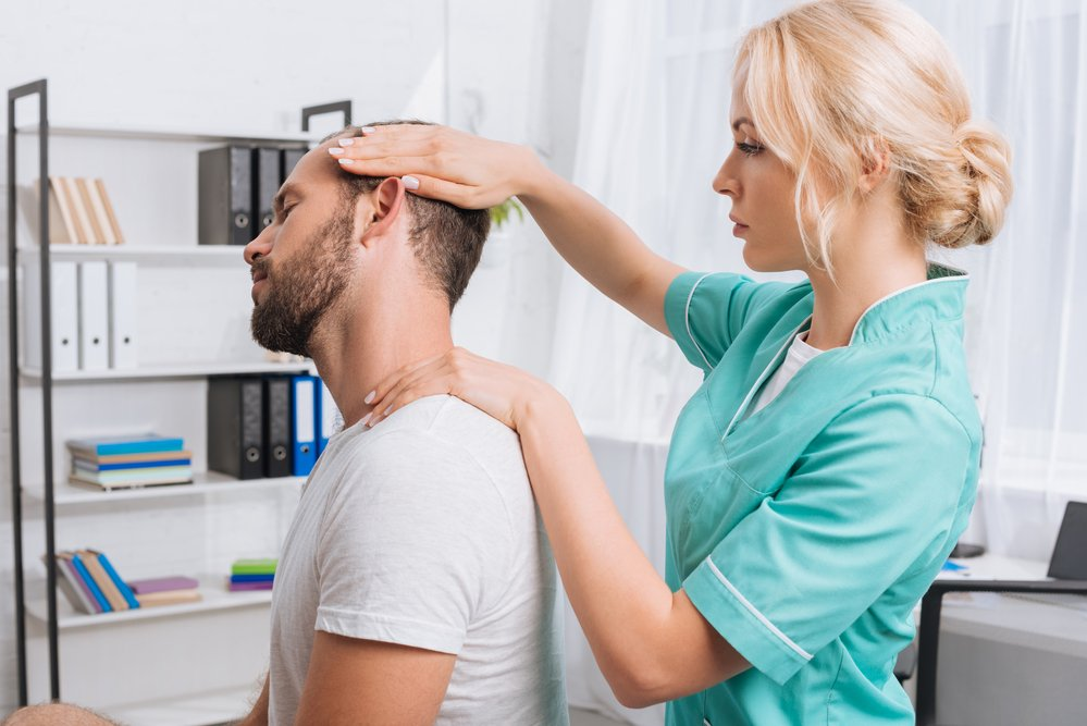 A female chiropractor giving chiropractic treatment to a male patient. She is working on stretching his neck.