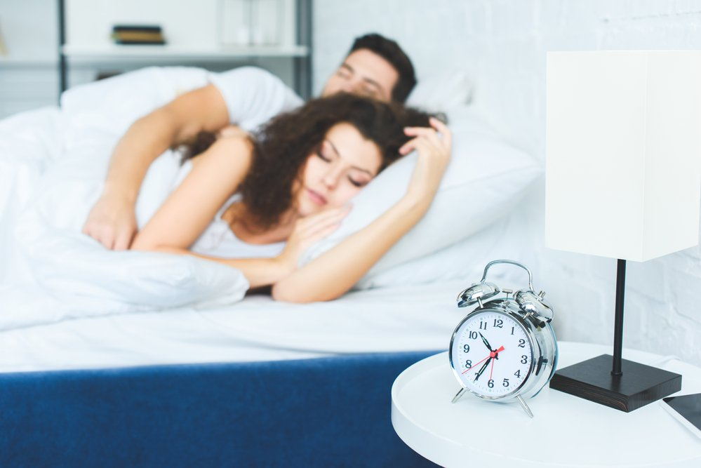 A couple sleeping in a bed with white linen and an alarm clock on the bedside. Invest in sleep for burning calories.
