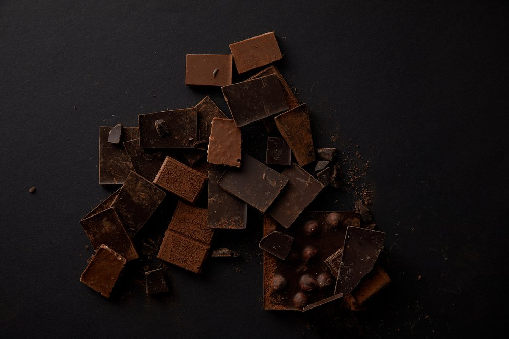 An aerial view of different types of milk and dark chocolate, some with nuts. Chocolate is one of the most common food cravings